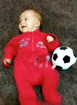 Three months and loving the soccer ball Granddad bought before she was born!